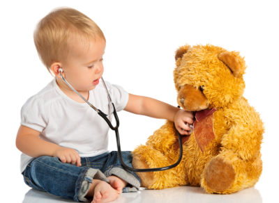 Baby plays with stethoscope and teddy bear